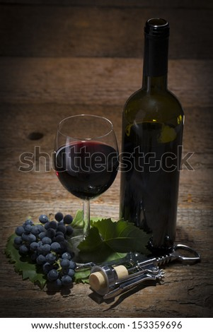 autumnal still life, grapes, cork screw, wine glass and wine bottle on wooden