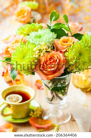 Autumnal table setting with  bunch of autumn flowers and cup of tea - stock photo