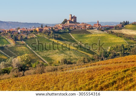 Autumnal vineyards and small town on the hill in Piedmont, Northern Italy. - stock photo