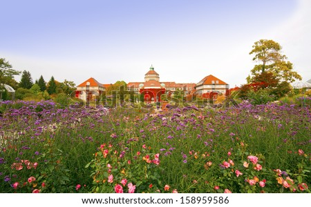Autumnal wide-angle view of the main building of the Botanical Garden in Munich, Bavaria-Germany with roses, wild flowers and red leaves - stock photo
