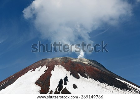 Avacha Volcano - active volcano of Kamchatka Peninsula. View of top of volcanic cone, fumarolic activity of volcano: steam and gas emissions from crater. Russia, Far East. - stock photo