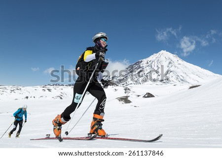 AVACHA VOLCANO, KAMCHATKA, RUSSIA - APRIL 26, 2014: Ski mountaineer climbs on skis on background volcano. Individual race ski mountaineering Asian, ISMF, Russian and Kamchatka Championship. - stock photo