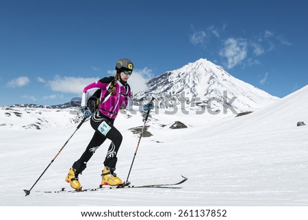 AVACHA VOLCANO, KAMCHATKA, RUSSIA - APRIL 26, 2014: Ski mountaineer Sorvinkova Tatiana climbs on skis on volcano. Individual race ski mountaineering Asian, ISMF, Russian and Kamchatka Championship. - stock photo