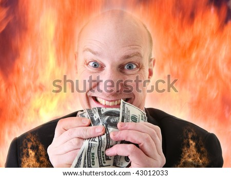 Avarice, businessman with money. man or devil holding dollars in display of greed in hell fire. A Deadly sin - stock photo