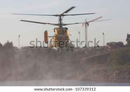 AVELAR, PORTUGAL - JULY 7 : Fire rescue heavy helicopter, with water bucket, scooping water in Avelar July 7, 2012 in Avelar, Portugal