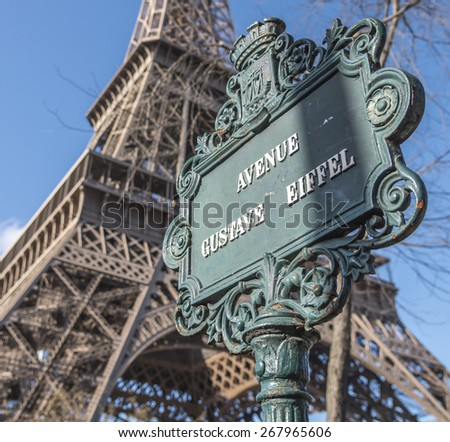 Avenue Gustave Eiffel street sign with the Eiffel Tower out of focus in the background. - stock photo