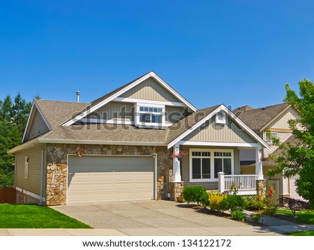 Average family house with concrete driveway to the garage. Blue sky background - stock photo