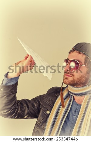 Aviator pilot with hat and sunglasses plays with paper planes - stock photo