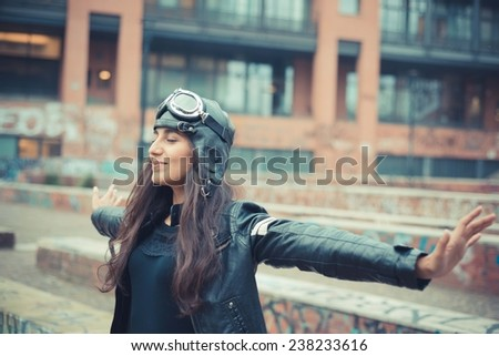 aviator young beautiful brunette woman with cap and glasses in the city - stock photo