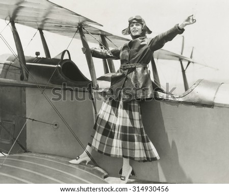 Aviatrix standing on bi-plane - stock photo