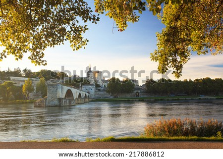 Avignon Bridge with Popes Palace and Rhone river at sunrise framed with sunny trees, Pont Saint-Benezet, Provence, France - stock photo
