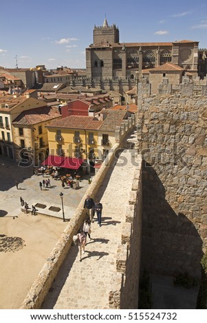 Avila, Spain - May 31, 2016: People walk on the city wall with the cathedral in the background in Avila, Spain on May 31, 2016