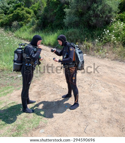AVLAKI,GREECE-JULY 04 2015 :Two female Scuba Divers walk to the sea with their equipment to go for a dive..Diving is an adventurous sport with dive sites in most countries around the world.