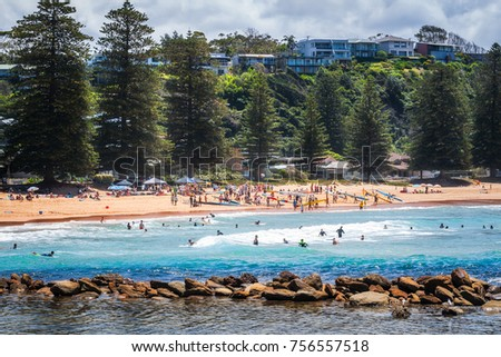 Avoca Beach, Central Coast, Australia - November 12, 2017: People enjoying a sunny day at Avoca Beach on the Central Coast, NSW, Australia. Local sport competition is about to start
