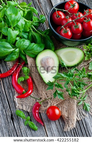 Avocado and branch of red ripe cherry tomatoes on  wooden board - stock photo