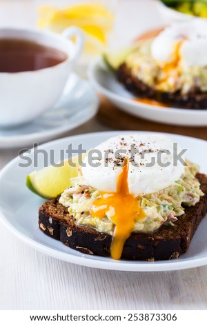 Avocado and feta smash on toasted rye bread and poached  egg on top, healthy breakfast - stock photo
