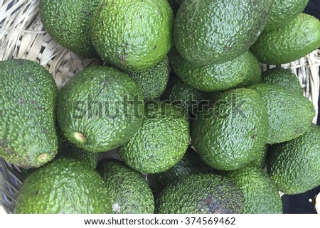 Avocado background. Fresh green avocado on a market stail. Food background. - stock photo