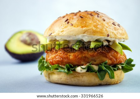Avocado fish sandwich with brioche bun , mayonnaise and lettuce - stock photo