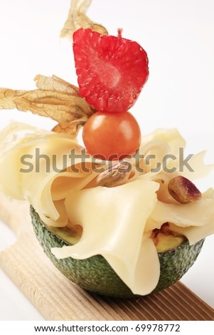 Avocado fruit and slices of Swiss cheese - stock photo