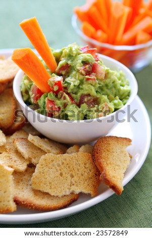 Avocado guacamole served with carrot sticks and bagel crisps - a healthy variation of this delicious snack. - stock photo
