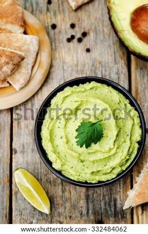 avocado hummus on a dark wood background. toning. selective focus - stock photo