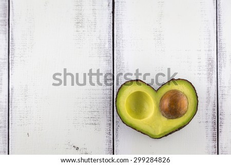 Avocado in the shape of a heart on a rustic white table - stock photo