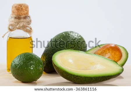 Avocado, lime and a bottle of oil on wooden table- spa, bodycare and haircare concept