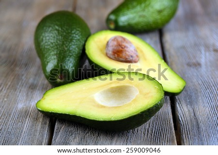 Avocado on wooden background - stock photo