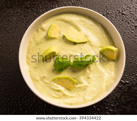 avocado paste garnished with basil and avocado slices - stock photo