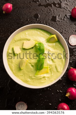 avocado paste garnished with basil ,radish and avocado slices on a wet ...