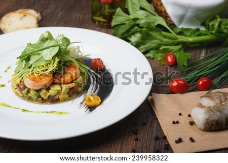Avocado salad with shrimp and quail eggs. - stock photo