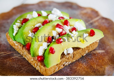 Avocado with Feta, pomegranate and olive oil on sunflower seeds bread sandwich. Healthy organic and vegan breakfast, on wooden background