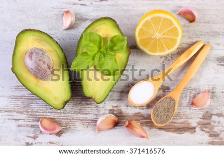 Avocado with ingredients and spices to avocado paste or guacamole, garlic, lemon, basil, concept of healthy food, nutrition and omega fatty acids - stock photo