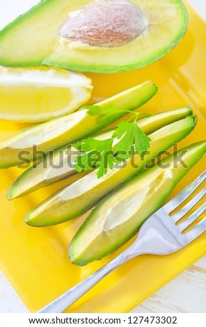 avocado with lemon on the yellow plate - stock photo