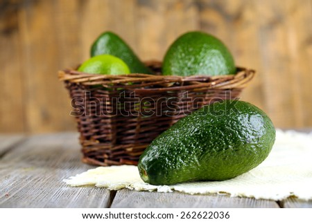 Avocado with limes in basket on wooden background - stock photo
