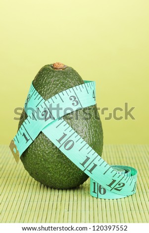 avocado with measuring tape on green background