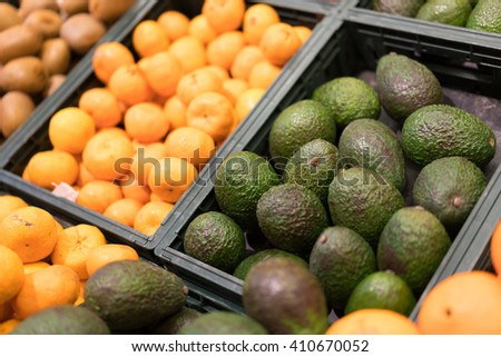 Avocados and oranges on fruit market - stock photo