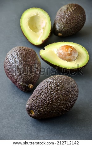 Avocados on black background, selective focus - stock photo