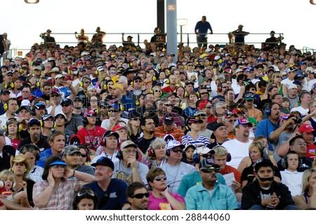 AVONDALE, AZ - APRIL 18: Fans in the grandstand watch the NASCAR Sprint Cup race at the Phoenix International Raceway on April 18, 2009 in Avondale, AZ. - stock photo