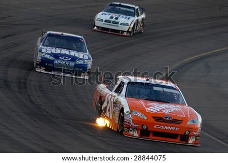 AVONDALE, AZ - APRIL 18: Joey Logano #20 leads a group of cars at the NASCAR Sprint Cup race at the Phoenix International Raceway on April 18, 2009 in Avondale, AZ. - stock photo