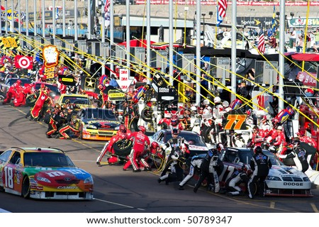 AVONDALE, AZ - APRIL 10: Pit crews change tires and refuel their cars during the Subway Fresh Fit 600 NASCAR Sprint Cup race on April 10, 2010 in Avondale, AZ. - stock photo