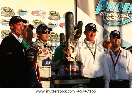 AVONDALE, AZ - NOV. 15:Jimmie Johnson (third from left) accepts the trophy for the Checker O'Reilly Auto Parts 500 at Phoenix International Raceway on Nov. 15, 2009 in Avondale, AZ. - stock photo