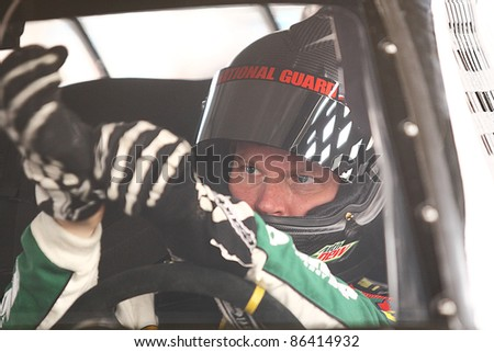 AVONDALE, AZ - OCT 4: Dale Earnhardt Jr. (88) puts his gloves on before heading to the track for a testing session on Oct. 4, 2011 at Phoenix International Raceway in Avondale, AZ. - stock photo