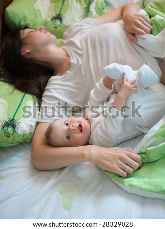 Awake baby with sleeping mom in a bed