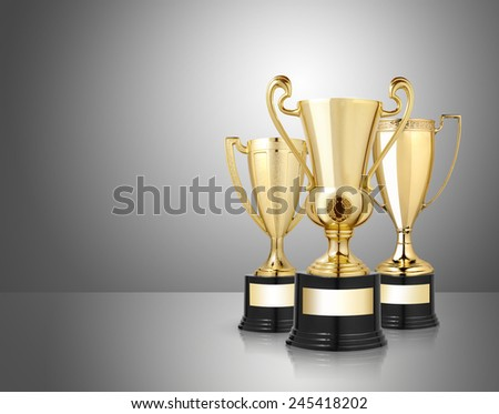 award golden trophies on gray background - stock photo