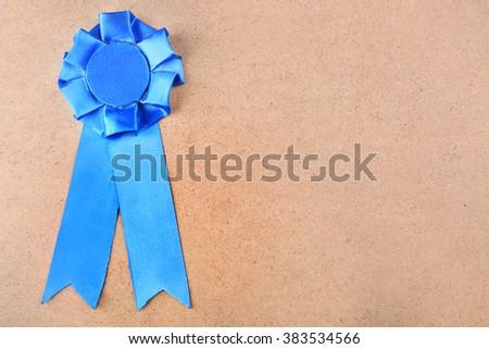 Award ribbon on wooden background - stock photo
