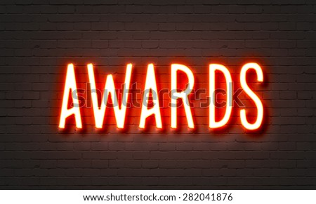 Awards neon sign on brick wall background