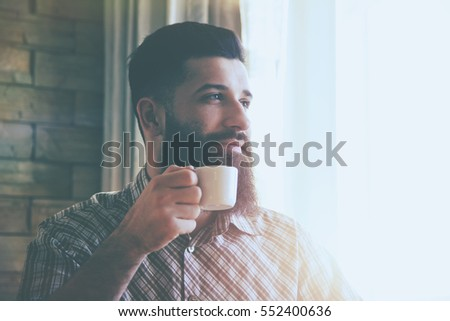 Awesome bearded man drinking cup of morning coffee