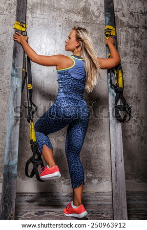Awesome blond female in leopard sportswear and  gym shoes posing between two columns after her exercises. View from behind. - stock photo