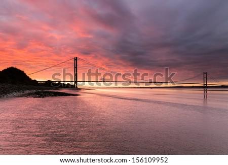 Awesome blood red, hellish sunrise over the Humber Bridge (UK) - stock photo